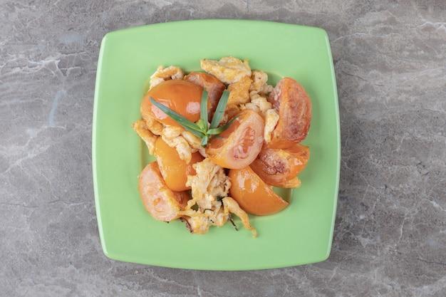 Jajko sadzone i pomidory na zielonym talerzu.