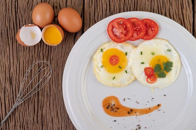 Jajko sadzone na białym talerzu z pokrojoną wiosenną cebulą i pokrojonymi pomidorami