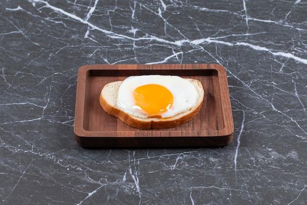 Jajko sadzone na chlebie pokrojonym na desce, na marmurowej powierzchni