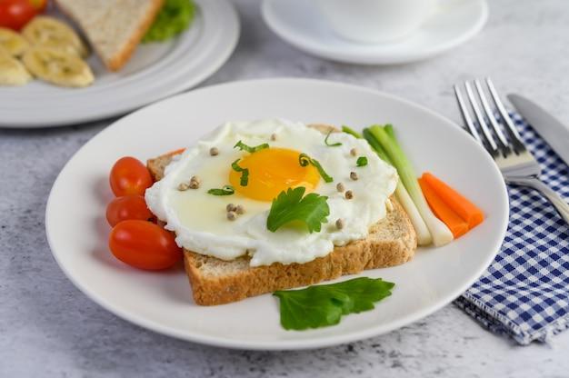 Jajko sadzone na grzance, zwieńczone ziarnami pieprzu z marchewką i dymką.