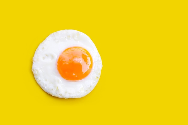 Jajko sadzone na żółtym tle. widok z góry