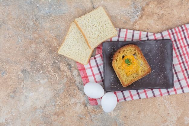 Jajko sadzone wewnątrz grzanki na czarnym talerzu z kromkami chleba