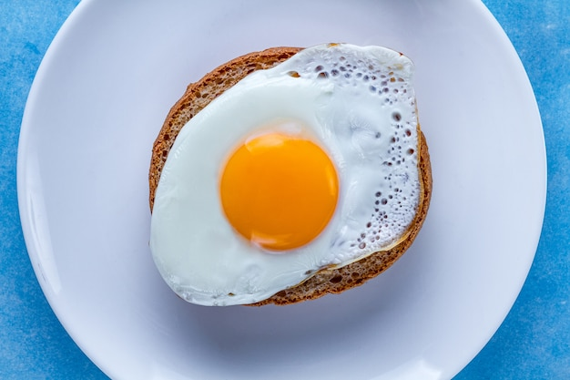 Jajko sadzone z kurczakiem i bułką na talerzu na zdrowe śniadanie. żywność białkowa. widok z góry