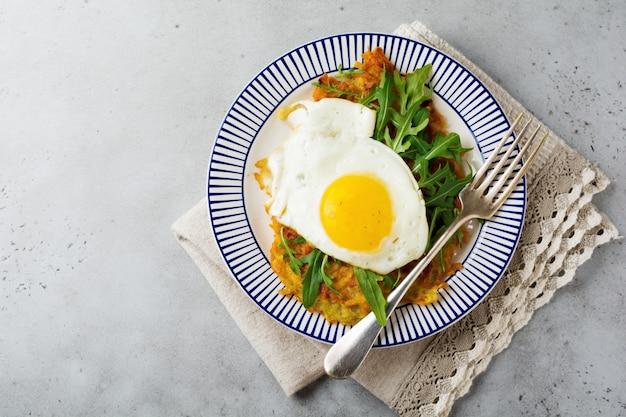 Jajko sadzone z plackiem ziemniaczanym, rukolą i awokado na talerzu ceramicznym na śniadanie. widok z góry.