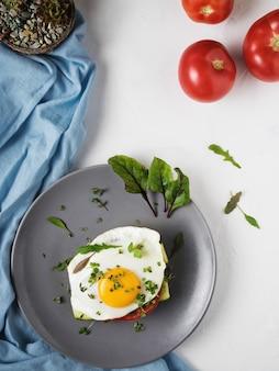 Jajko sadzone z pomidorami i liśćmi rukoli i tymianku na pieczywie na szarym talerzu