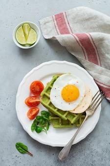 Jajko sadzone z serem, pomidorami, boćwią i waflem ze szpinakiem na białym talerzu ceramicznym na jasnoszarym betonowym stole. kanapka na śniadanie. selektywna ostrość. widok z góry. skopiuj miejsce.
