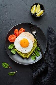 Jajko sadzone z serem, pomidorami, boćwią i waflem ze szpinakiem na czarnym talerzu ceramicznym na ciemnym betonowym stole. kanapka na śniadanie. selektywna ostrość. widok z góry. skopiuj miejsce.