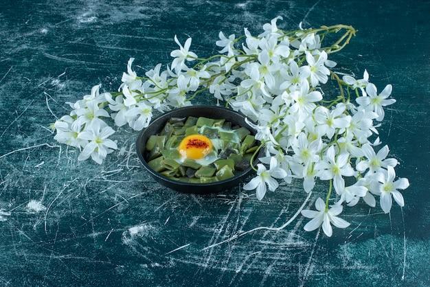 Jajko sadzone z zieloną fasolką na patelni. zdjęcie wysokiej jakości
