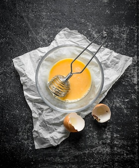 Jajko ubić w misce trzepaczką na papierze. na ciemnej rustykalnej powierzchni