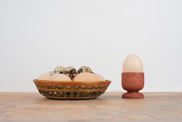 Jajko w filiżance i kilka jaj przepiórczych w koszu.