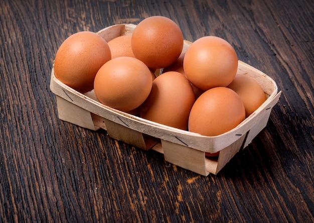 Jajko w koszu na drewnianym stole