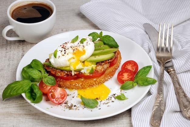 Jajko w koszulce na opiekanym kawałku bagietki pomidor pikantna szynka awokado posypane przyprawami i bazylią