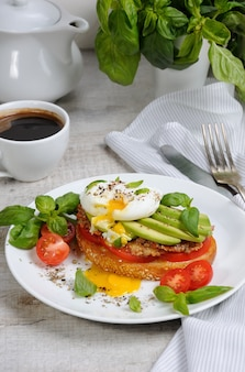 Jajko w koszulce na opiekanym kawałku bagietki z pikantną szynką pomidorową i awokado