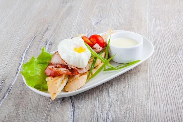 Jajko w koszulce z boczkiem pomidorki koktajlowe cebula na bagietce i białym sosie