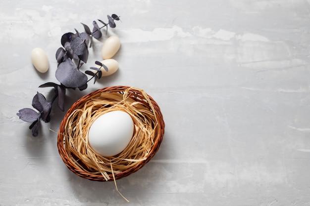 Jajko w koszyczku na jasnoszarym tle