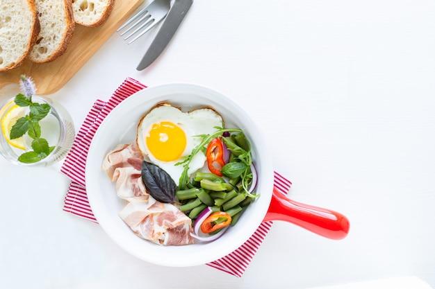 Jajko w kształcie serca, bekon, fasolka szparagowa na patelni, chleb na desce do krojenia i woda z cytryną