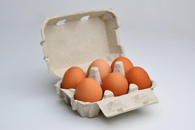 Jajko w papierowym pudełku na białym tle