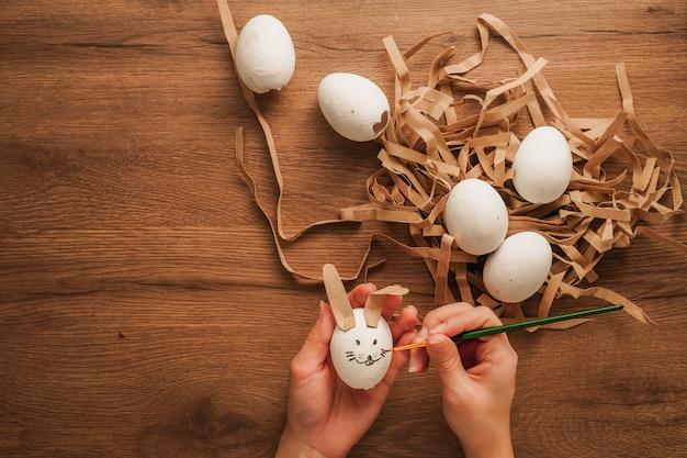 Jajko w ręku jak twarz królika i inne białe jajko na drewnianym stole