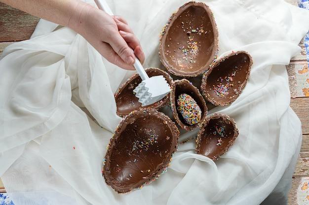 Jajko wielkanocne, które właśnie zostało podzielone młotkiem, odsłaniając kilka połówek, które były wewnątrz siebie (pisanka pinata).
