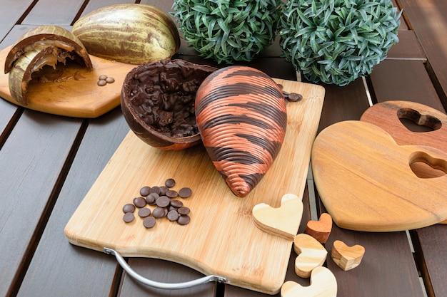 Jajko wielkanocne z gorzkiej czekolady z chrupiącymi migdałami, ozdobione jadalną farbą, na drewnianej desce. otoczony czekoladowymi kaletkami, drewnianymi serduszkami i czekoladowym jajkiem z karmelowym nadzieniem.