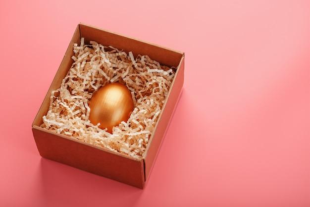 Jajko wykonane ze złota w drewnianym pudełku na różowym tle. pojęcie wyłączności i superprize. minimalistyczna kompozycja.