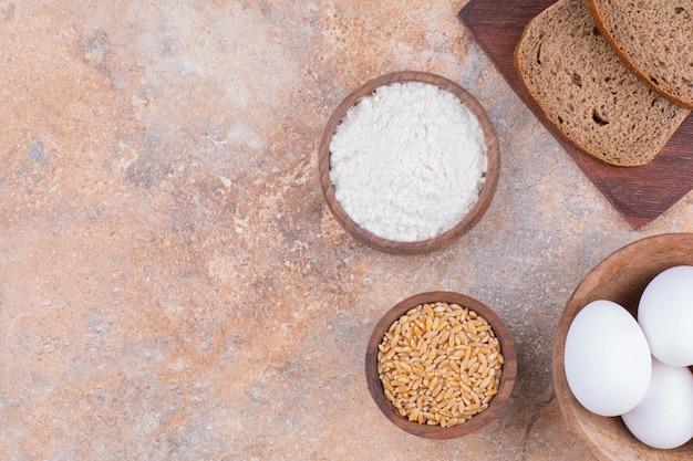 Jajko, ziarno, mąka i krojony chleb na desce, na marmurze.