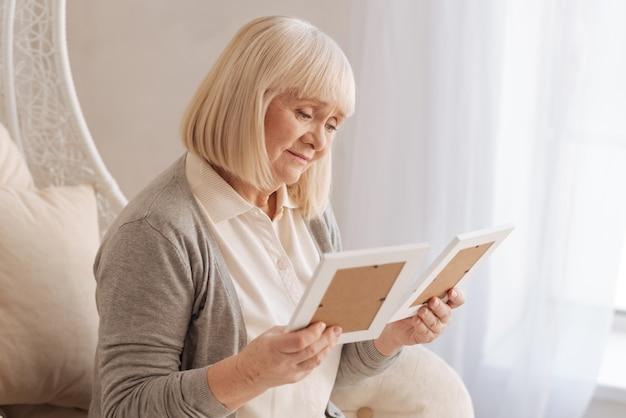 Jak będę żyć bez ciebie. beztroska nieszczęśliwa starsza kobieta myśli o swoim mężu i tęskni za nim, patrząc na zdjęcia