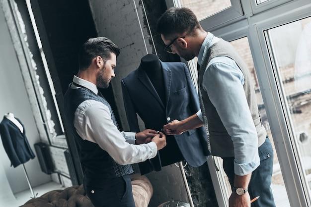 Jak ci się podoba ten? dwóch młodych modnych mężczyzn dotykających kurtki stojąc w warsztacie