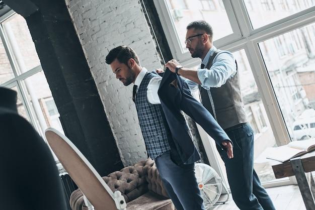 Jak ci się to podoba? młody modny projektant pomagający swojemu klientowi się ubrać
