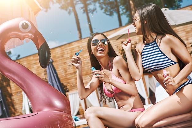 Jak dzieci, dwie piękne i szczęśliwe młode kobiety w strojach kąpielowych bawią się dmuchaniem baniek