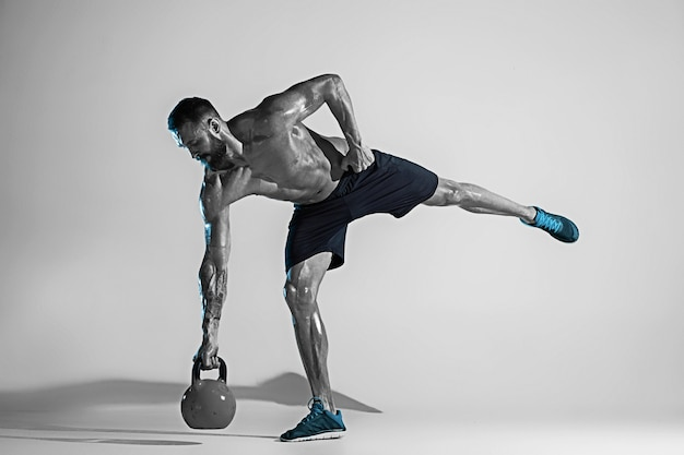 Jak kamień. młody kulturysta kaukaski szkolenia na tle studia w świetle neonu. muskularny model męski z wagą. pojęcie sportu, kulturystyki, zdrowego stylu życia, ruchu i działania.