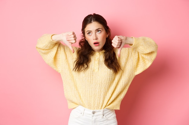 Jak kiepsko. niezadowolona i obojętna młoda kobieta przewraca oczami, wzdycha i patrzy na bok, pokazując kciuki w dół ze sceptyczną twarzą, stojąc pod różową ścianą