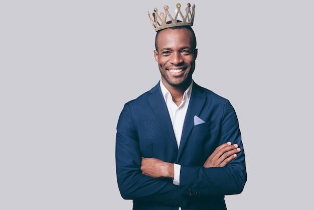 Jak król. przystojny młody afrykański mężczyzna w koronie i eleganckiej kurtce na co dzień, patrząc na kamerę i uśmiechając się na stojąco
