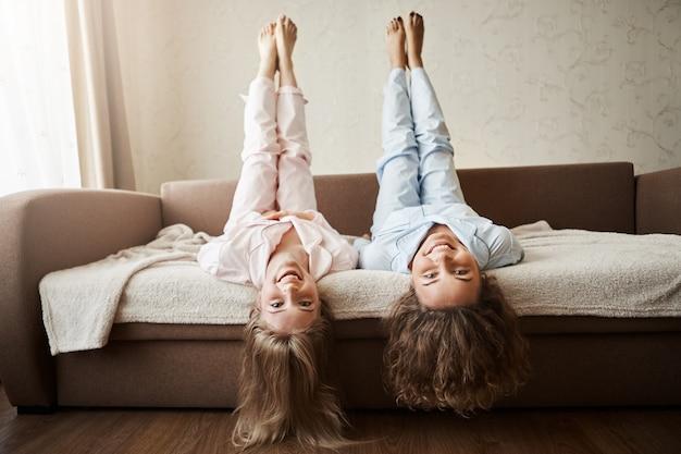 Jak miło jest leżeć i wygłupiać się z dziewczyną przez cały dzień. urocze dziecięce europejskie kobiety leżące na kanapie w nocnej bieliźnie z uniesionymi dłońmi i głową do góry nogami, włosy dotykają podłogi, uśmiechają się szeroko