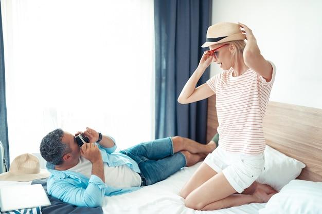 Jak model. piękna kobieta w słomkowym kapeluszu i okularach przeciwsłonecznych w kształcie serca pozuje mężowi z aparatem.