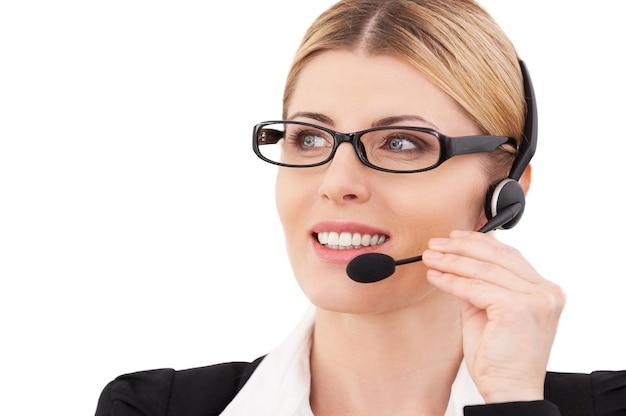 Jak mogę ci pomóc? pewna siebie dojrzała przedstawicielka obsługi klienta dostosowująca zestaw słuchawkowy i uśmiechająca się, stojąc na białym tle