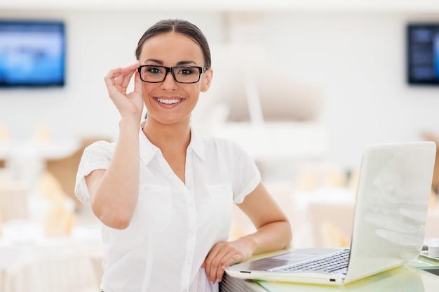 Jak mogę ci pomóc? piękna młoda kobieta w formalnym stroju dopasowująca okulary i uśmiechająca się, opierając się o kontuar barowy