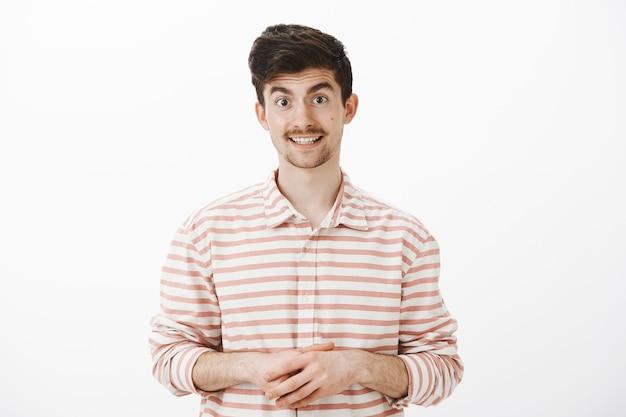 Jak mogę ci pomóc. portret przyjaznego, przystojnego sprzedawcy z europy w koszuli w paski, trzymającego się za ręce i oferującego pomoc, rozmawiającego swobodnie i grzecznie z klientem przez szarą ścianę