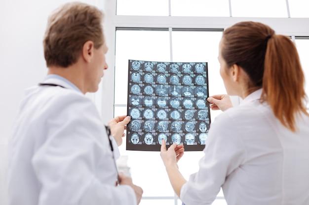 Jak mogę pomóc. doświadczony, uważny i kompetentny neurochirurg, który podczas omawiania diagnozy z innym lekarzem zwraca uwagę na niektóre kwestie oceniając na podstawie skanów mózgu pacjenta