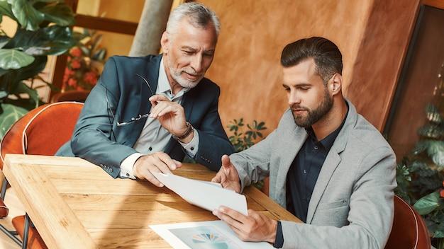 Jak możemy to ulepszyć biznesmeni dyskutujący o nowych pomysłach podczas przerwy obiadowej