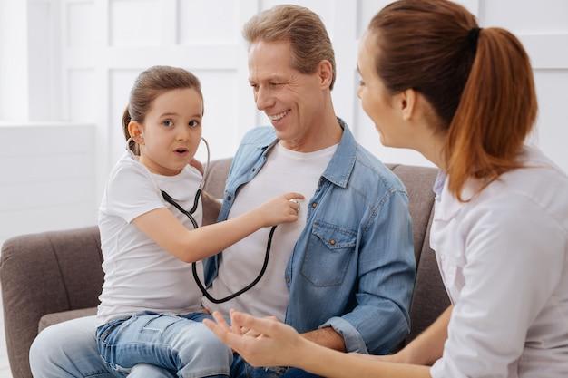 Jak pielęgniarka. zaciekawiona, urocza młoda pacjentka używa stetoskopu lekarza na swoim ojcu, bawiąc się podczas składania wizyty