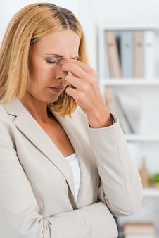 Jak przetrwam ten dzień? przygnębiona dojrzała bizneswoman dotyka nosa
