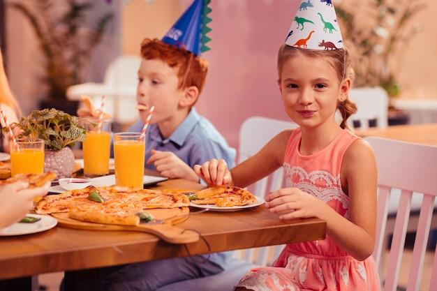 Jak słodko. wesoła mała suczka utrzymująca uśmiech na twarzy podczas jedzenia pizzy