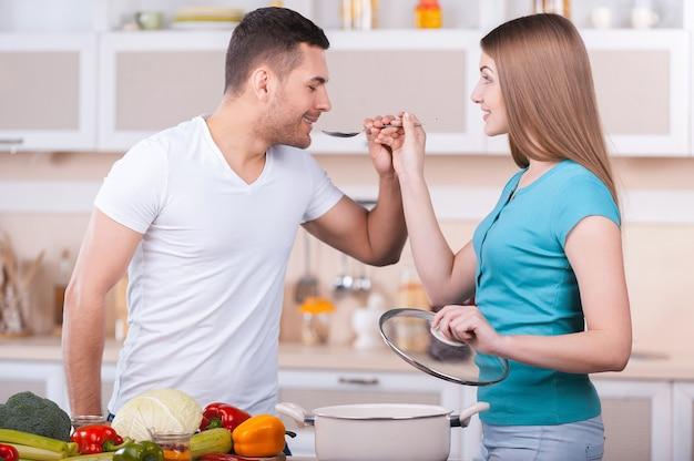 Jak smakuje ta zupa? piękna młoda kobieta karmi swojego chłopaka zupą stojąc razem w kuchni