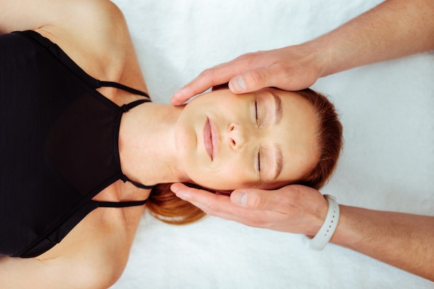 Jak spokojnie. widok z góry na spokojną twarz kobiety leżącej na łóżku medycznym