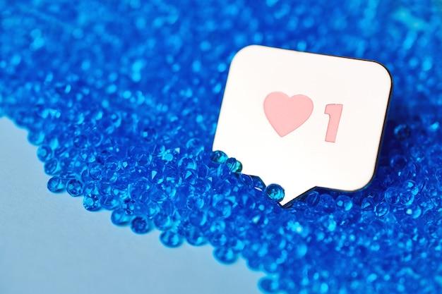 Jak symbol serca. jak przycisk znaku, symbol z sercem i jedną cyfrą. marketing sieciowy w mediach społecznościowych. niebieski brokat diamentowe tło.
