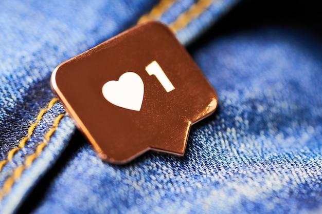 Jak symbol serca. jak przycisk znaku, symbol z sercem i jedną cyfrą. marketing sieciowy w mediach społecznościowych. niebieskie dżinsy tekstura tło.