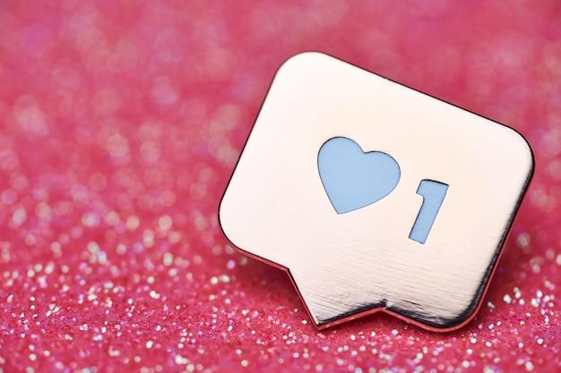 Jak symbol serca. jak przycisk znaku, symbol z sercem i jedną cyfrą. marketing sieciowy w mediach społecznościowych. różowy brokat iskry tło.