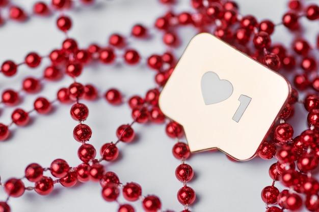 Jak symbol serca. jak przycisk znaku, symbol z sercem i jedną cyfrą. marketing sieciowy w mediach społecznościowych. tło koraliki czerwony brokat.