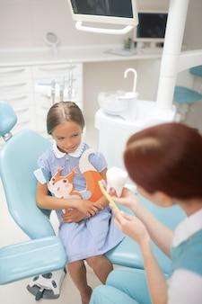 Jak szczotkować. dziewczyna czuje ciekawość, słuchając dziecka dentysty pokazującego, jak myć zęby